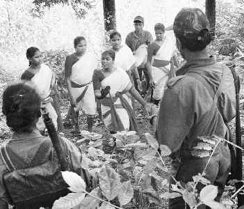 Amred members of the CPI (ML) People's War watch artistes of the Jana Natya Mandali singing revolutionary songs in a remote area in the Sileru forest area of the Visakha agency
