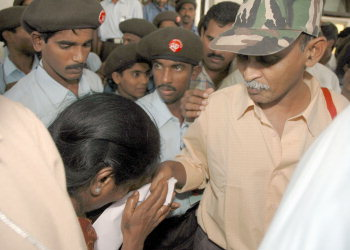 HYDERABAD : A woman  weeps at the hands of Ramakrishna while presennting him a plea outside the Manjira Guest house before he left for the final round of talks at the MCR Human Resources Development Institute in Hyderabad on Monday .. -- PHOTO: P_V_Sivakumar / 18-10-2004